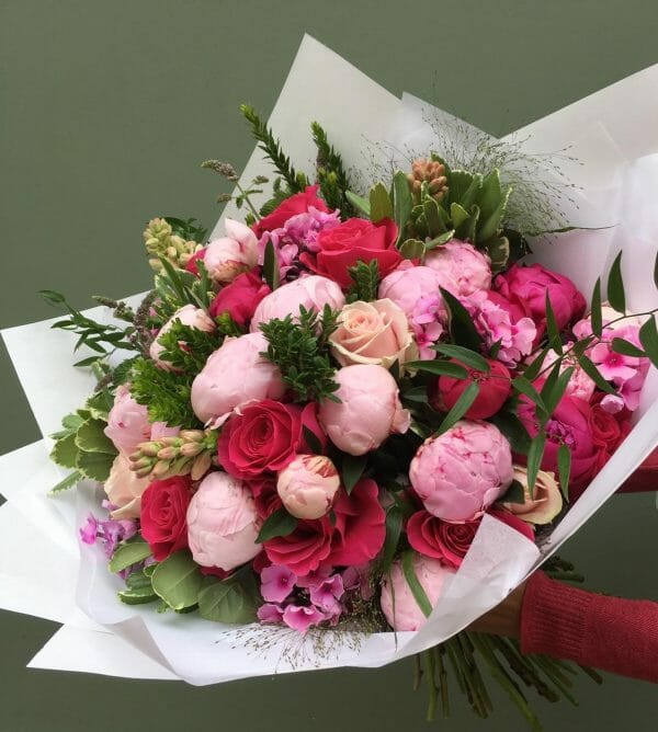 Photograph of a vivid seasonal hand tied bouquet available from Kensington Flowers London