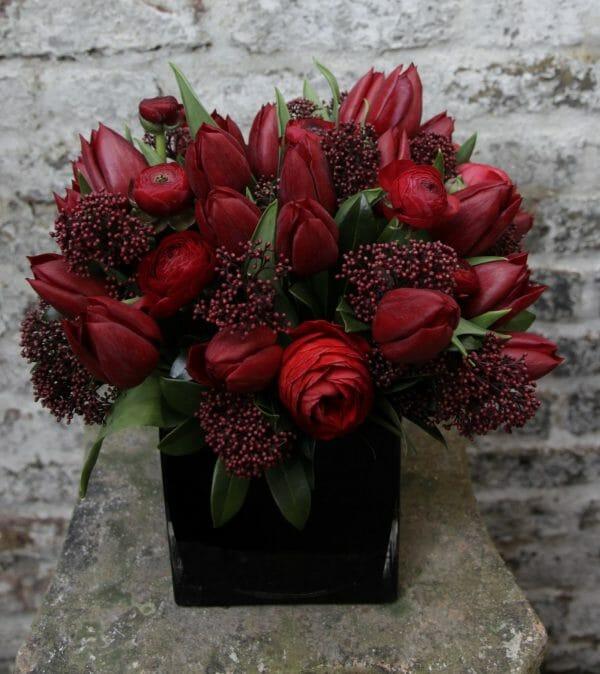 Photo showing a sample of a Studio Vase Arrangement - Red spring flowers - Kensington flowers, London