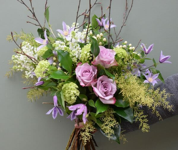 Photo showing a sample of a seasonal Rose bouquet with clematis available from Kensington flowers