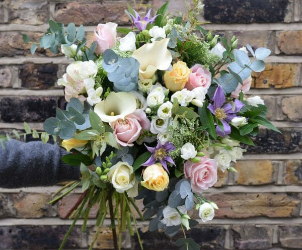 Photo of a Seasonal Rose Bouquets in pastel colours roses, freesia, calls lily, clematis included in sample from Kensington flowers