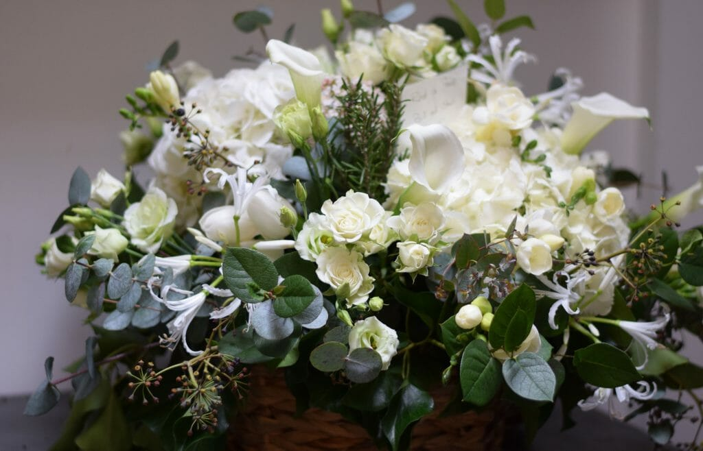 Photo of a basket arrangement of all white flowers funeral flowers from Kensington flowers