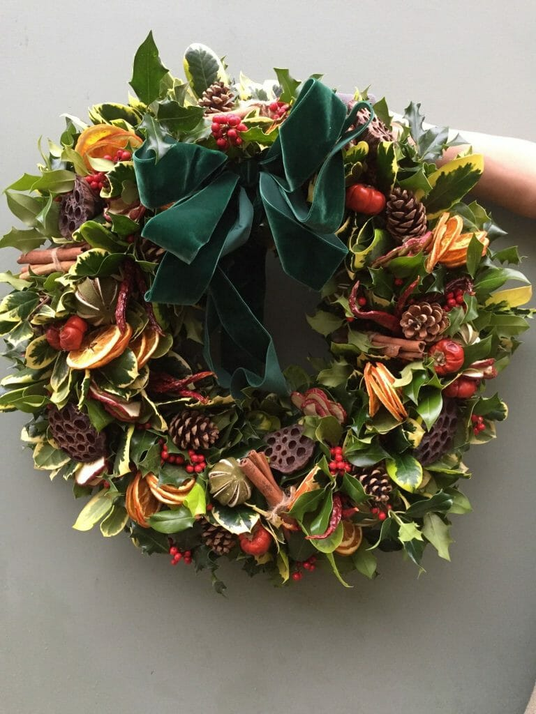 Photo showing a sample of a Holly, fruits, cones and lotus seed heads Christmas door wreath From Kensington flowers London