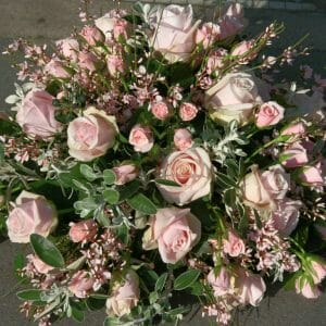 Photo of a pink funeral flowers Posy sympathy tribute arrangement, available to order from Kensington flowers