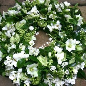 Photo showing a sample of a White funeral wreath spring flowers available at Kensington flowers London