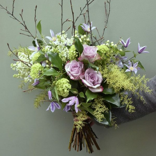 Photo showing a sample of a seasonal rose bouquet with lilac clematis available from Kensington flowers