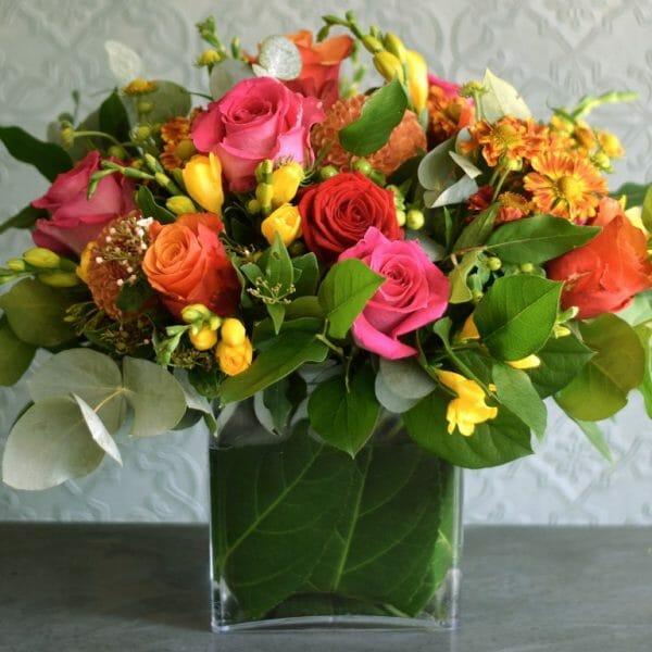 Photo showing a sample image of seasonal vase arrangement mixed vivid colours Kensington flowers