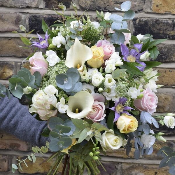 Photo of a Seasonal Rose Bouquets in pastel colours roses, freesia, calls lily, clematis included in sample from Kensington flowers London