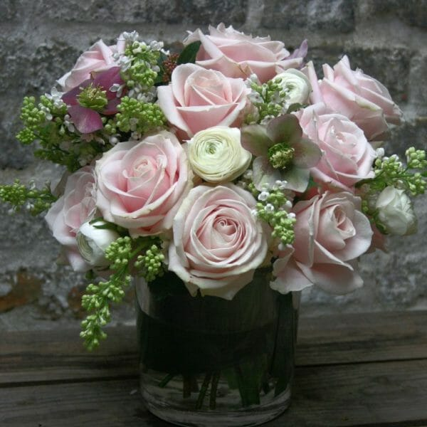 Photo showing a sample of a seasonal rose , florist choice vase arrangeemnt of roses and helebores, available from Kensington flowers Ltd
