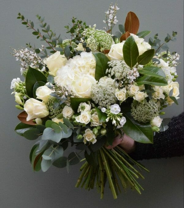 Photo showing a sample of a white and cream seasonal hand tied bouquet available to order from Kensington Flowers London